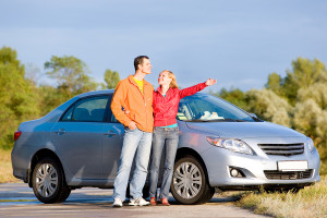 Happy young couple with their new car. Woman show something by h